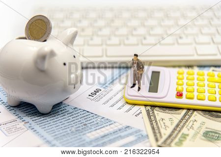 Miniature businessman calculating tax for income tax return for saving tax target for save coin in the piggy bank. Tax and Saving Concept