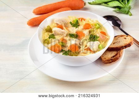 A photo of a plate of chicken, vegetables, and noodles soup, shot on a light texture with slices of bread, carrots, and a spoon, selective focus and copy space