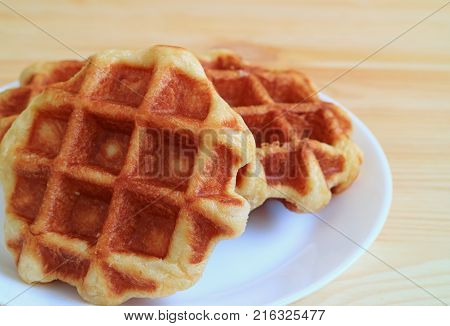 Closed up a pair of Belgian Waffle on White Plate Served on Wooden Table