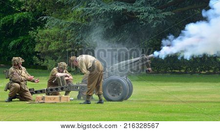 SILSOE, BEDFORDSHIRE, ENGLAND - MAY 28, 2017:  Second World War Field Gun Being Fired gunners wearing Uniforms.