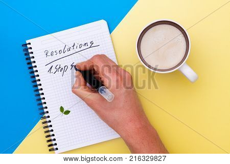 Top view on writing men hand in notebook and near cup of coffee separated on yellow and blue paper background.. Hand write the new year resolutions.
