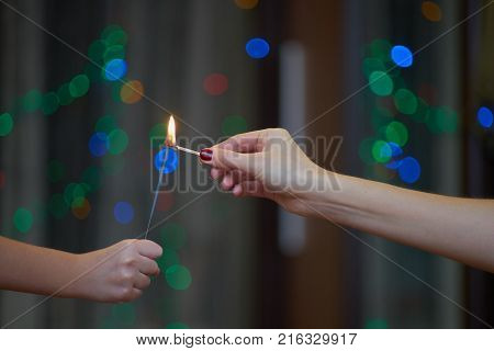 Two people are igniting sparkler with a match There are two human hands. Little girl is holding a sparkler and her mother is igniting it with a match. Bokeh bubbles are on blurred background. The photo is dark.