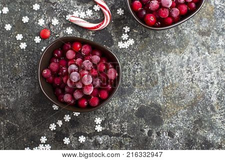 Frozen cranberries in a white enameled vintage bowl on a plain gray background with a beau enameled spoon. Top View