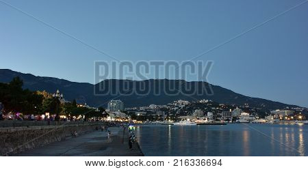 YALTA CRIMEA SEPTEMBER 13 2017: Holidaymakers on the embankment of Yalta after sunset