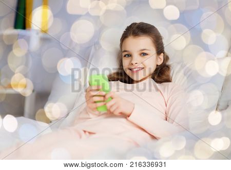 people, children and technology concept - happy smiling girl lying awake with smartphone in bed over holidays lights background