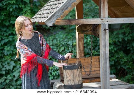 Russia Moscow Izmaylovsky Park August 27 2017. International Photo Festival.A Russian woman in a scarf with a bucket at the well. Russian woman. A woman with a Russian handkerchief.