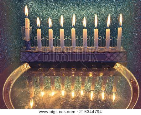 Jewish holiday Hanukkah celebration with menorah and lights of burning candles