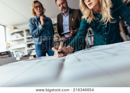 Team of architects working on construction plan. Designers working on blueprint on table in office. Focus on female hand pointing on drawing.