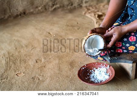 Close up hands holding bowl with copra and adding milk to it to cook dough