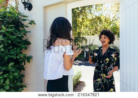 Excited african woman attending a female friend's housewarming party. Woman giving a wine bottle her friends at entrance door.