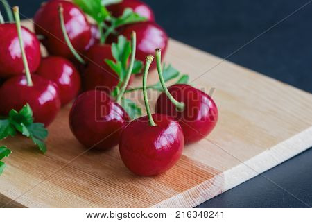 Close up fresh cherries on wood cutting board. Red cherry put on black granite table in side view with copy space. Cherry have high vitamin C and have sweet and sour taste. Healthy friut concept of red cherry. Delicious and sweet cherry.