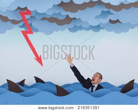 Businessman surrounded by sharks in stormy sea and business graph down. Competitive business concept.