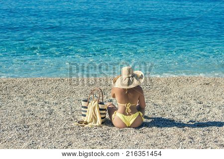Beautiful female in a yellow bikini with beach bag on the sand.  Beach holidays of beautiful girl.