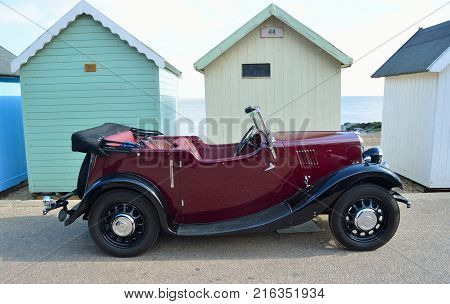 FELIXSTOWE, SUFFOLK, ENGLAND -  MAY 07, 2017: Classic Red Motor Car Parked on Seafront Promenade parked in front of beach huts.