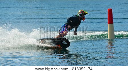 WYBOSTON, BEDFORDSHIRE, ENGLAND - JULY 08, 2017: Male Motosurf Competitor Taking corner at speed creating a lot of spray.
