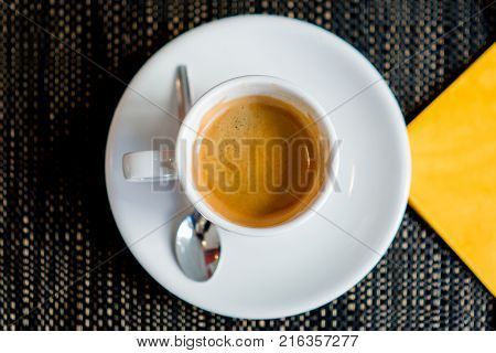 Espresso coffee flay lay in cafe with yellow napkin