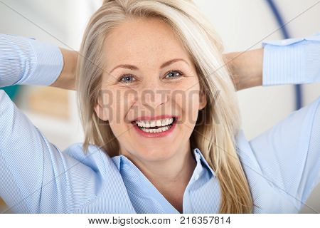 Modern businesswoman. Beautiful middle aged woman looking at camera with smile while siting in the office. Female face close-up