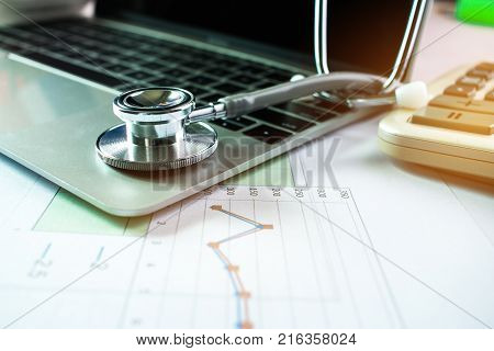 Stethoscope with prescription test results in Doctor consulting room background and calculator for medical costs in modern hospital on Laptop desk. Healthcare costs business and fees concept.
