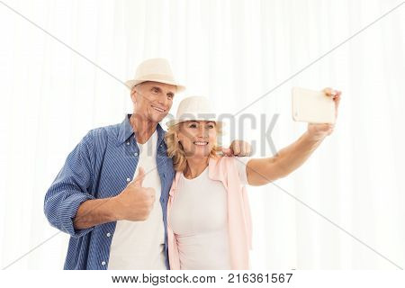 An elderly woman and elderly man at the airport making selfie. Elderly woman taking a photo and smiling. Elderly couple in a bright waiting room