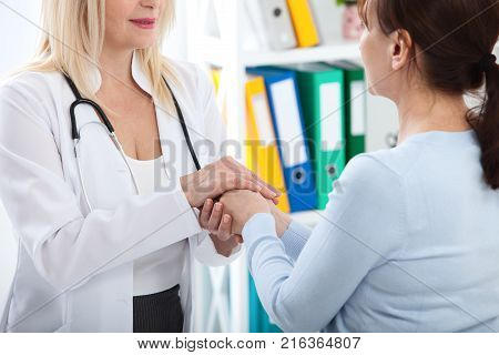 Hand of doctor reassuring her female patient. Medical ethics and trust concept