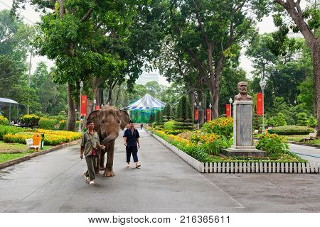Ho Chi Minh city Vietnam - September 01 2015: Zookeeper walks elephant in Saigon zoo and botanical garden. Popular place to visit on day tour for families traveling with kids.