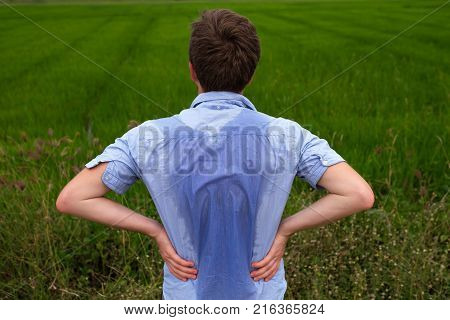 Man with hyperhidrosis sweating very badly under armpit in blue shirt because of hot weather. Travelling in asia thailand with backpacker