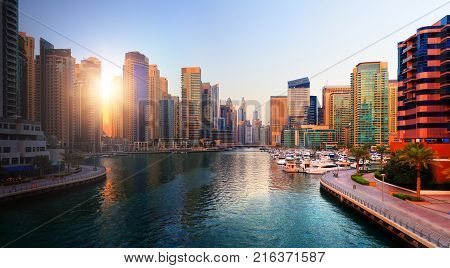 Dubai evening skyline. Luxury district in Dubai at the sunset. Sun shines through skyscrapers at marina in Dubai.