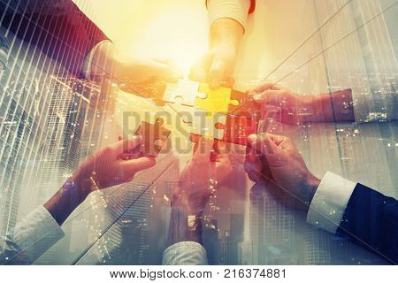 Businessmen working together to build a colored puzzle. Concept of teamwork, partnership, integration and startup. double exposure