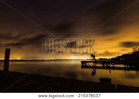 Long exposure photography of a female photographer at lake Pobles Del Sud pier near Valencia, Spain
