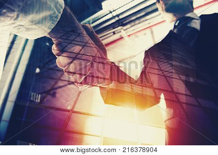 Handshaking business person in the office. concept of teamwork and business partnership. double exposure