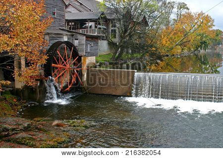 water turns the wheel of a gristmill surrounded by autumn foliage