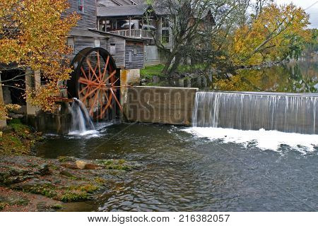 a gristmill next to a dam surrounded by autumn foliage