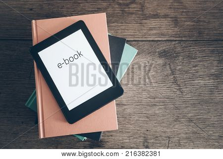 e-book reader on a stack of books on rustic wooden table concept