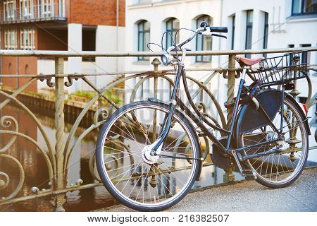 vintage bicycle parked against iron handrail on a bridge across a channel in Hamburg Germany
