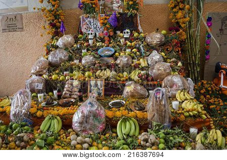OAXACA, OAXACA, MEXICO- OCTOBER 30, 2017: Traditional offering altar with flowers, fruits, religious images and candles for mexican Day of the Dead celebration in Oaxaca, Mexico