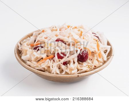 Traditional russian appetizer sauerkraut with cranberry and carrot in craft plate isolated on white. Fermented cabbage. Russian cuisine and russian kitchen.