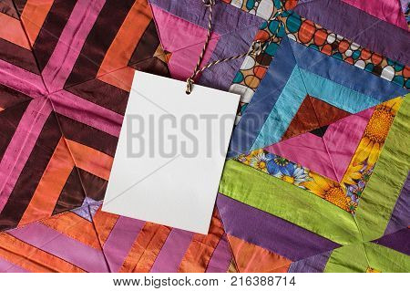 handcraft, creating, gifting concept. there is white clean card for greeting on amazing quilt of marvelous bright colours and with different floral and geometric patterns