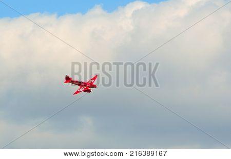 OLD WARDEN, BEDFORDSHIRE, ENGLAND - AUGUST 06, 2017:  DH88 De Havilland Comet  flying  Cloudy Sky.