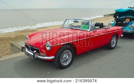 FELIXSTOWE, SUFFOLK, ENGLAND -  MAY 07, 2017: Classic Red  Triumph Spitfire  Convertible  Motor Car Parked on Seafront Promenade.