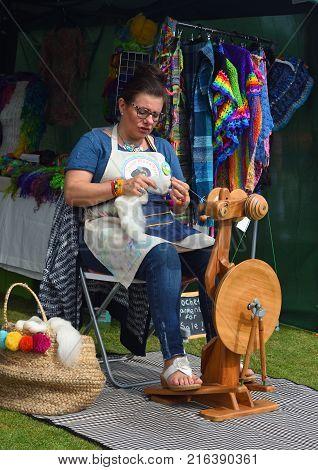 FELIXSTOWE, SUFFOLK, ENGLAND - SEPTEMBER 03, 2017:  Woman Spinning wool at traditional spinning wheel.