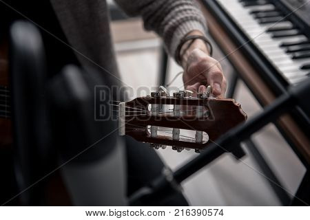 Close up of male hands tuning a guitar in studio. Synthesizer is on background