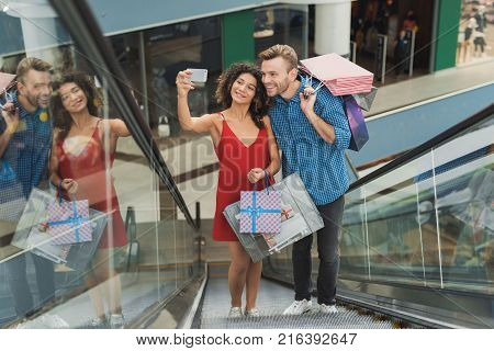 The girl and her boyfriend are shopping at the mall. Sale on a black Friday. A young couple are shopping on a black Friday. The girl is making a selfie with her boyfriend on an escalator in the mall.