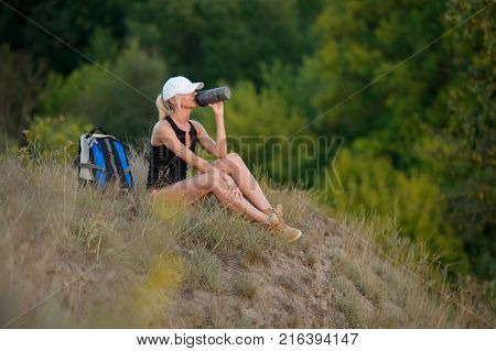 Pretty hiker girl drinking water. Thirsty woman tourist with backpack drinks water outdoors. Refreshing healthy lifestyle concept
