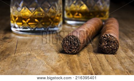 Two Cuban cigars with two glasses of whiskey on an old wooden table with a blurred background