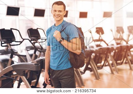 A young man is posing in the gym. A muscular man in a blue T-shirt is smiling. Behind him are simulators.
