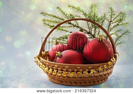Christmas card. Christmas background with a basket with red balls and bokeh lights. In a beautiful basket are red matte balls.