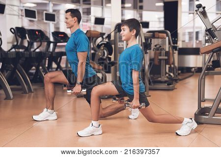 Father with his son in the same clothes in the gym. Father and son spend time together and lead a healthy lifestyle. A man with a boy is engaged with a dumbbell.
