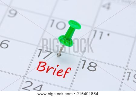 Brief written on a calendar with a green push pin to remind you and important appointment.