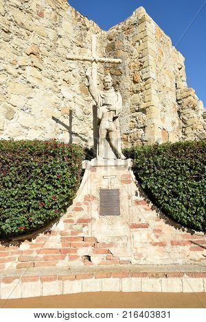 San Juan Capistrano, Ca - December 1, 2017: Father Junipero Serra with Indian Child Statue, on the mission grounds with the Great Stone Church Ruins.