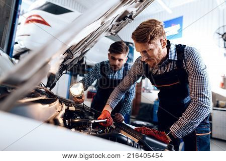 Father and son work at the auto service. Two mechanics work with the details of the car. Two mechanics dig under the hood of the car.